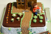 Image: A single tier cake with a character reading a gardening book surrounded by his cabbages