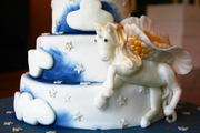 Image: A three-tier celebration cake with a prancing pony character