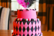 Image: A three-tier celebration cake pink and black icing and a shower of feathers exploding from the top