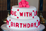 Image: A two-tier birthday cake with a pink marzipan bear topper
