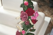 Handmade sugar roses in deep claret, cyclament and pink with wheat and rose foliage