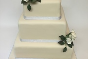 Mix flavour sponges, finished ivory sugarpaste and pale blue organza ribbon - Hand made cream roses and foliage complete theis simply elegant cake