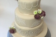 "Three tiered, different flavours, finished in vintage cream with hand made ""amnesia roses"", piped pearls, brushed embroidered rose motifs and a vintage lace"