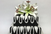 2 tierd square stacked - rich chocolate bottom and vanilla sponge top.  Finished in black and white sugarpaste with hand made sugar lilies