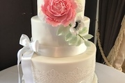Three Tiered stacked wedding cake with fruit bottom, chocolate middle and vanilla sponge top.  Hand made sugar peony, anemonies and rununculus flowers and hand made sugar lace.