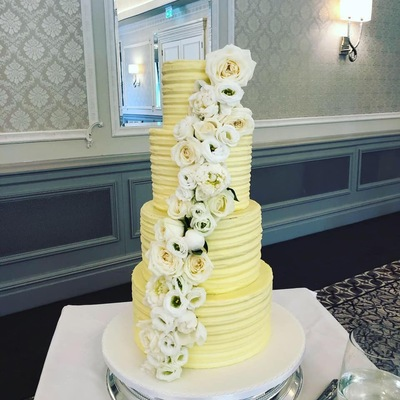 Four tiers of different flavoured sponges covered in vanilla butter cream and finished with real flowers